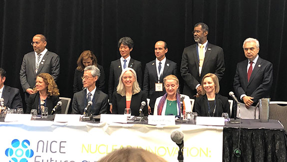 Photo of a diverse group of participants – 5 women and 6 men, half seated and half standing – at the Clean Energy Ministerial 10 meeting.