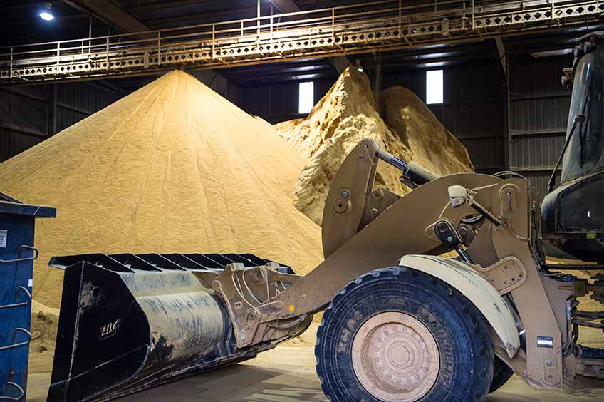 Photo of a warehouse containing a large pile of grains with a yellow tractor in the foreground.