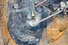 Photo of a mining operation from above, yellow mining equipment in the center, surrounded by orange soil, rocks and two mining chutes.