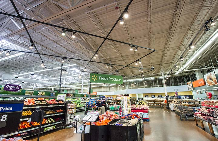 Photo of a grocery store, LED lighting hangs from the ceiling. Bins with fruit are in the foreground, a bakery on the front righthand side of the photo.