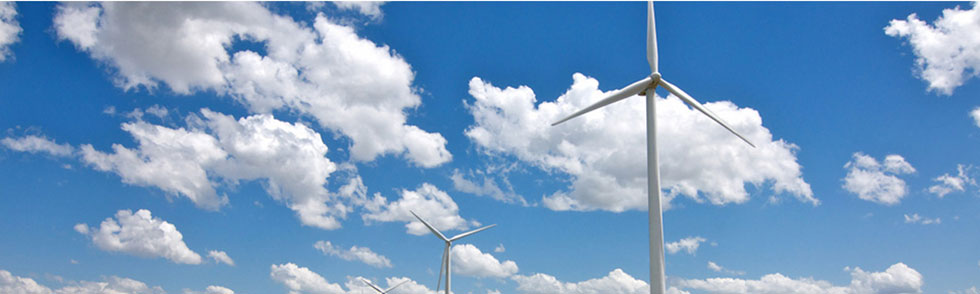 Wind turbines against a sky with puffy white clouds.