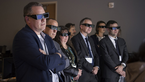 A photo of business men and women wearing sunglasses standing in a dark room.